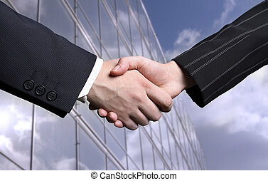 business hand shake and a office in background,