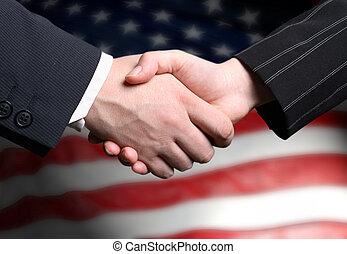 hand shake and a American flag in the background - hand...