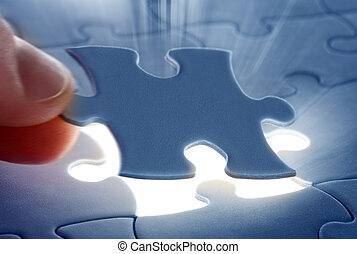 last piece of a Puzzle - Hands placing last piece of a...