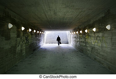man passing through underpass - shadowy man passing through...