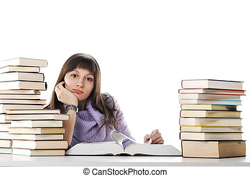 Tired of studies, A beautiful young woman sitting at a desk with two large piles of books.