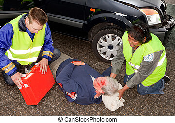 Paramedics with injured man - Car crash victim being helped...