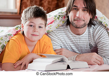 Dad and son reading in bed