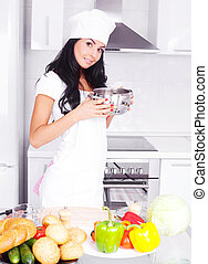 woman cooking - beautiful brunette woman cooking in the...