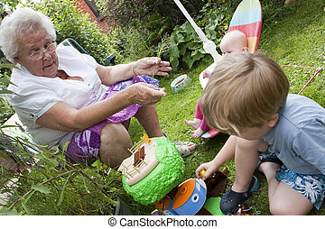 Gran and gran children playing outside in the garden -...