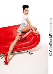 Leggy Retro Model On Red Leather Sofa