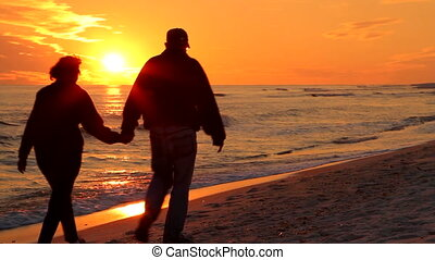 Couple Walking Away At Sunset - Retired man and woman stroll...