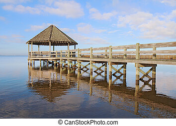 Gazebo, dock, blue sky and clouds over calm sound waters -...