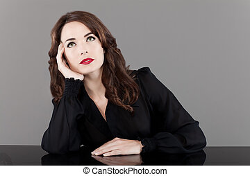 Portrait of a beautiful middle aged woman with red lips looking up  thinking pensive on gray background