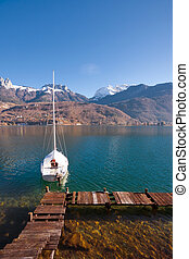 Anchored Sailboat Alps Lake - A sailboat is anchored on a...