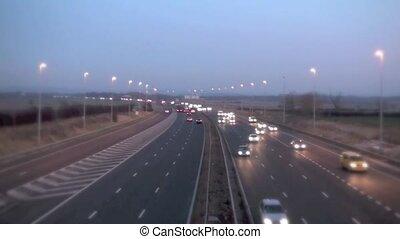 Motorway day to night - Motorway traffic speeding past as...