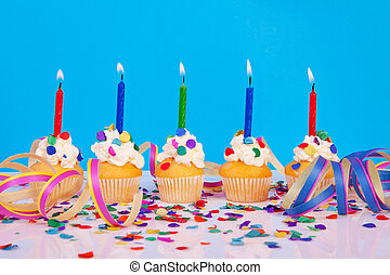 Birthday cupcakes with candle streamers and colorful confetti