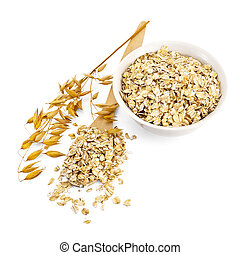 Rolled oats in a bowl and spoon - Rolled oats in a wooden...