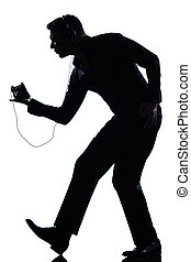 silhouette man full length dancing happy listening to music...
