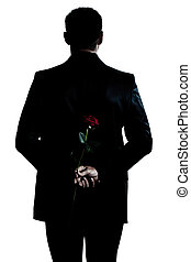 rear view silhouette man portrait holding a rose flower -...