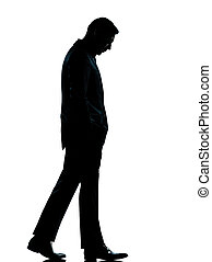 one business man walking looking down silhouette - one...