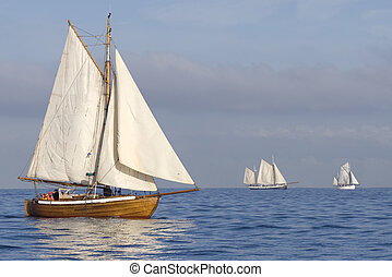 Tender with white sails - Three ships with white sails in...