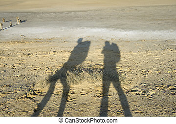 Shadows of two travellers against barren dry landscape