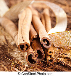 a few cinnamon sticks on wooden background an a golden bow