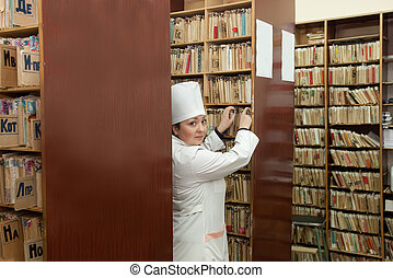 Nurse searching medical chart in clinic