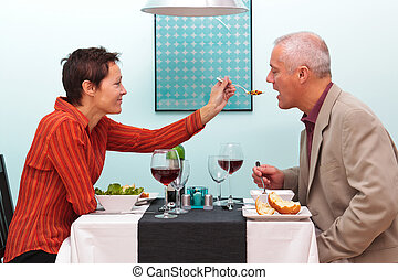 Married couple sharing food in a restaurant