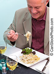 Man eating pasta in a restaurant