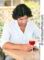 Man reading with a glass of rose in the sunshine