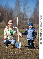 woman with boy planting tree - woman and boy with spade...