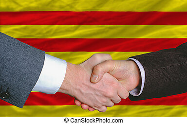 two businessmen shaking hands after good business investment agreement in front of flag of catalonia