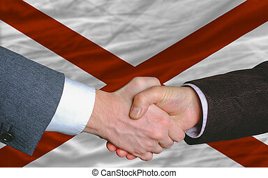 two businessmen shaking hands after good business investment agreement in front US state flag of alabama