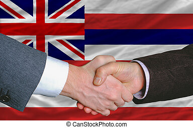 two businessmen shaking hands after good business investment agreement in front US state flag of hawaii
