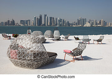 Cafe chairs with view of Doha downtown skyline, Qatar,...