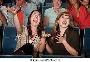 Laughing Women in Audience - Young women laugh out loud in...