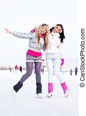 girls ice skating - two beautiful girls ice skating outdoor...