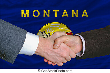 two businessmen shaking hands after good business investment agreement in front US state flag of montana