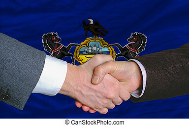 two businessmen shaking hands after good business investment agreement in front US state flag of pennsylvania