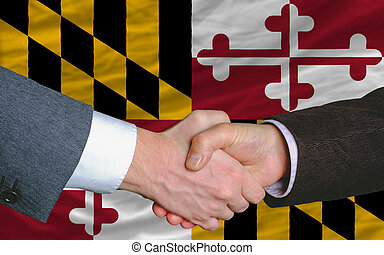 two businessmen shaking hands after good business investment  agreement in front US state flag of maryland