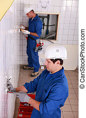 Electricians working in a tiled room