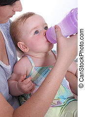 Mother feeding her baby water from a large baby bottle