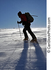 Back country skier (ski touring), walking up to a snowed...