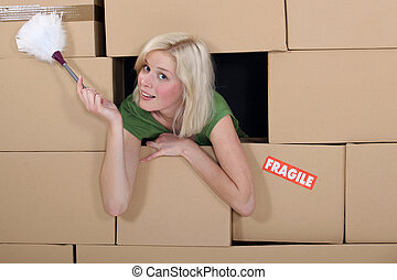 Woman with a feather duster surrounded by packing boxes