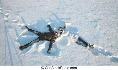 Snow angels - Young couple lying on snow and making snow...