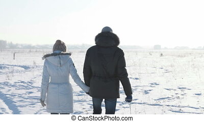 Walking with sledges - Young people walking across the snowy...