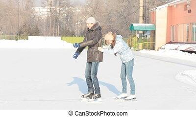 Funny skating couple - Dolly shot of girl pushing his...