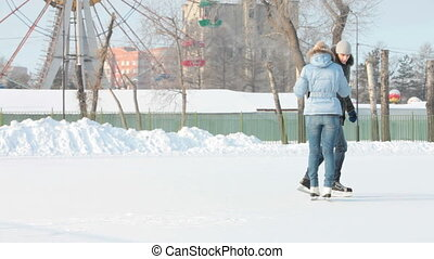 Skating couple - Dolly shot of couple skating on an open...
