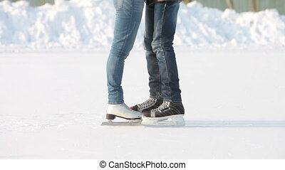 Skating and kissing - Tilt up of couple on skates kissing in...