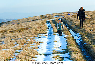 Family walk on autumn mountain plateau with first winter...