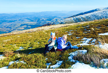 Children (small boy and girl) rest on autumn  mountain plateau with first winter snow