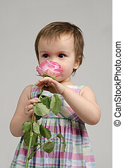 Adorable baby girl smelling pink rose
