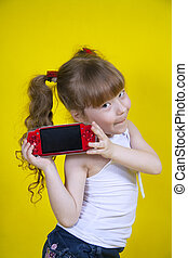 Little girl playing handheld portable game console. Yellow...